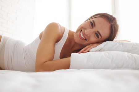 whiteness: Close-up of attractive dark-haired female in white tank top lying on white pillows against sunlit whiteness of the room Stock Photo