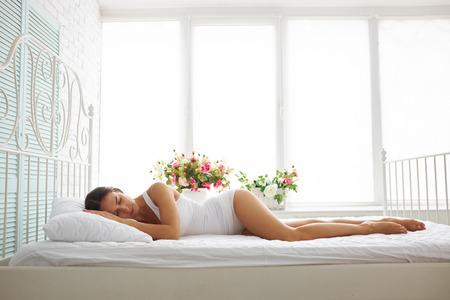 atmosfera: Mujer delgada atractiva en ropa interior blanca está durmiendo en la cama con sábanas blancas de la sala blanca con flores en el alféizar de la ventana