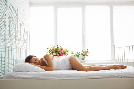 woman in bed: Sexy slim woman in white underwear is sleeping on bed with white sheets in white room with flowers on the windowsill Stock Photo
