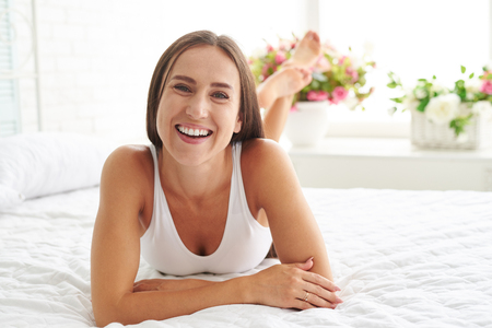 carelessness: A woman lying on the bed looking forward and smiling while enjoying a carelessness morning at home