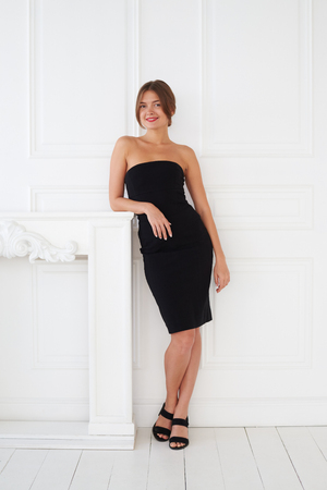 ladylike: An elegant ladylike girl with red lips and in a small black dress has a photo session in the photo studio Stock Photo