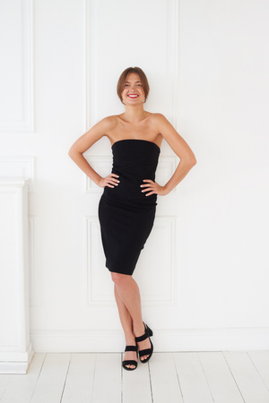 A beautiful full length portrait of a smiling, fancy lady in a black dress with sweet red lips, a gleam in her eyes and ivory skin