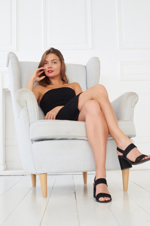 chic woman: Magnificent look of a chic woman in a sharp black dress sitting on a white sofa.  Black clothes and white background is the best contrast for brilliant photos Stock Photo