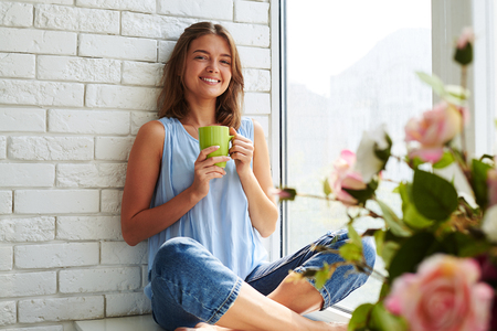 softly: While thinking about plans a young pretty girl smiling softly and frankly. Sitting on the window-sill and drinking a cup of aroma coffee Stock Photo
