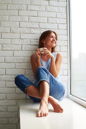 niña pensando: chica joven encantada que está pensando y mirando por la ventana mientras está sentado en el alféizar de la ventana y beber una taza de café aroma Foto de archivo