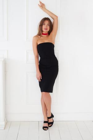 mujeres morenas: modelo europeo adornado bien en un vestido negro posa con su mano hacia arriba. Esta actitud hace la foto especialmente calientes