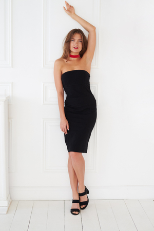 ladylike: Well-graced European model in a black dress poses with her hand up. This attitude makes the photo especially hot Stock Photo