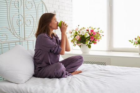 relaxing at home: Charming young woman is sitting at the bedside in pajamas and drinking tea on the background of big sunlit window with flower pot Stock Photo