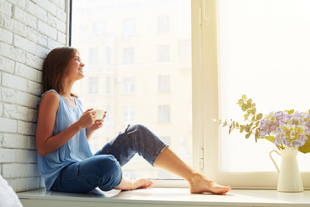 Thoughtful and dreaming girl looking out of the window on a busy city while sitting on the window-sill and holding a cup of aromatic coffee