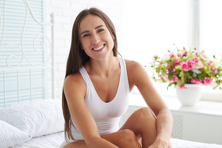 softly: Close-up portrait of a joyful and laughing softly woman with legs crossed sitting on the bed while posing at camera against the white view with multicolored flowers