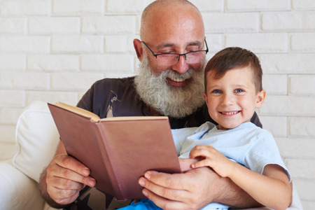 teaching: Portrait of stylish aged man sitting in armchair with his grandson and reading a book in living room