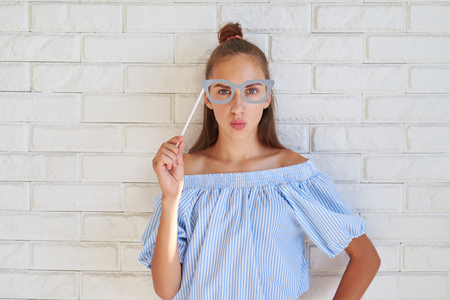 puckering lips: Cool Caucasial girl wearing paper glasses puckering lips while posing at the camera