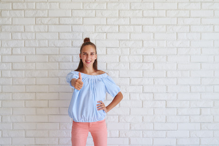 bollos: Close-up portrait of a cute girl showing thumb up standing against white background