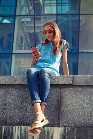 hustle: Smiling girl holding a phone while sitting on the concrete bench in the downtown. Relaxed and pleased in the hustle and bustle of the city