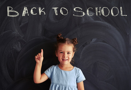 grade school age: Small princess in a light-blue dress with a cute haircut showing finger against back to school chalk inscription on blackboard