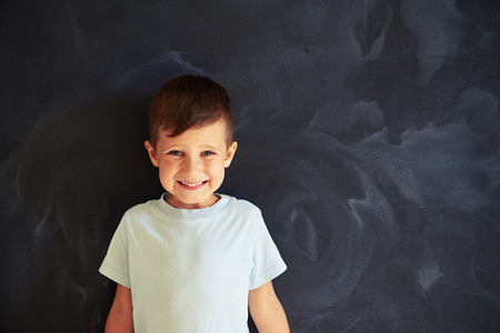 sincerely: Small boy is standing against blackboard and smiling sincerely