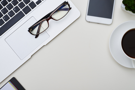 Top view of white office with empty space in the middle and frame of laptop, glasses, smartphone and cup of coffee