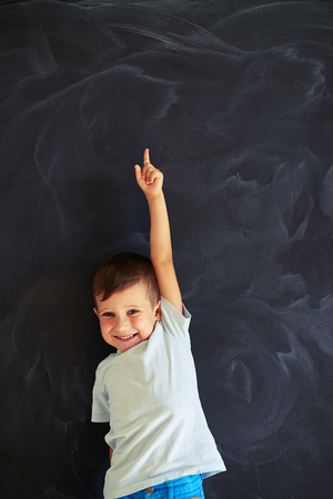 school boy: Cute small boy is smiling and pointing upwards with forefinger of stretched arm against school blackboard background