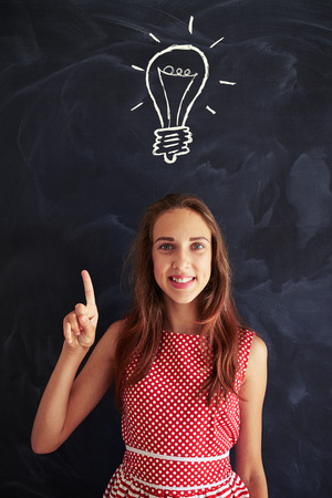 Concept of having a new idea is performed by smiling teenage girl standing against blackboard with chalk drawing of light bulb on it