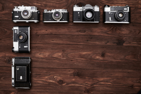 surface level: A shot of 6 black vintage cameras lying on the plain brown wooden surface. Some of objects are placed horizontally and some are in vertical order