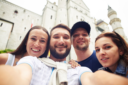 unpretentious: Mid shot of two men and two women standing in front of the fortress, wearing light clothes, smiling at the camera and taking photos. The unpretentious majestic grey architectural fortification castle stands behind them Stock Photo