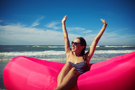 rejoicing: A shot of a young smiling lady sitting and rejoicing on a pink air rubber boat holding her hands up and showing her palms to the sun. Woman wearing blue swimming suit with white stripes on a glorious sunny day on the seaside