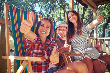 side shot: Low angle side shot of 3 people showing thumbs up while sitting on comfortable summer beach chairs at a resting house