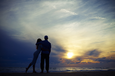 Wide low angle shot warmth embracing of happy romantic couple in love on the beach at sunset. People in love. Spending time together. Romantic atmosphere Stock Photo