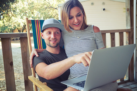 lap of luxury: Close-up of a man who is showing something interesting at the screen while a young woman is sitting on his laps. Showing photos that were made during the rest. Spending time together Stock Photo