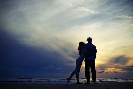 Wide low angle shot of the silhouette of loving couple. Spending vacation together near the sea. Romantic evening. Admiring the wonderful sunset. The sun I going down, the afterglow of sunset lingering on the horizon Stock Photo
