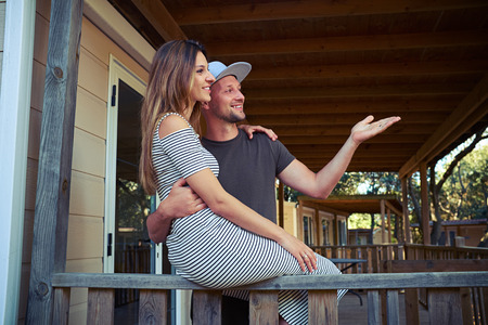 far off: Close-up of a young couple who is happy to see their friends far off. An attractive young Caucasian brunette is sitting on the handrail and hugging her husband
