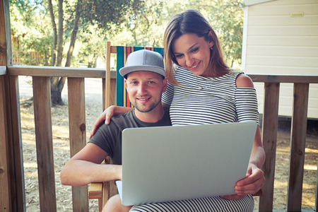 lap of luxury: Close-up of young couple who is sitting together on a summer beach armchair and looking at the screen of a laptop