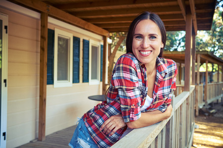 side shot: Close-up side shot of a toothy smile of relaxed woman who is leaning on the handrail near the wooden rest house. Spending summer vocation. Having a rest. Wearing light summer casual checked shirt and denim shorts. Taking photos Stock Photo