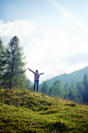 majestic mountain: Mid low angle shot of positive woman who is spreading hands and feeling the freedom on the mountain peak on a fair day. Stunning vista of the mountain valley covered with majestic forests