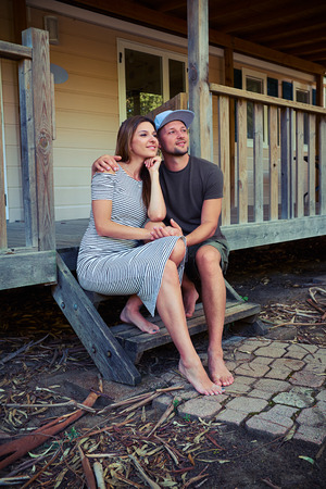 far off: Mid shot of a thoughtful romantic couple who is sitting on the stairs and looking far off. Sitting on the stairs of the modern wooden rest house. Spending vacation together
