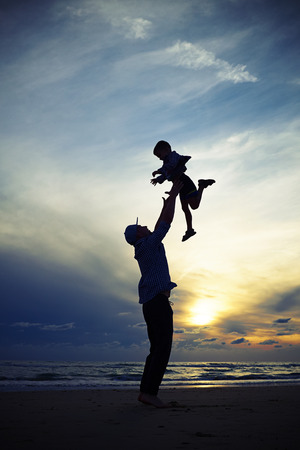 father and son: Mid low angle shot of the dad silhouette tossing up a child at the sunset while standing on the beach Stock Photo