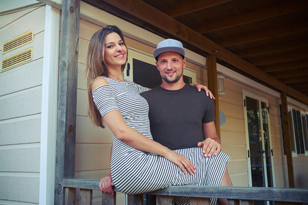 lap of luxury: Close-up of an attractive young Caucasian who is sitting on the handrail and hugging her husband. Wearing striped dress. Posing at the camera and taking photos. They stand on the terrace of the wooden rest house Stock Photo