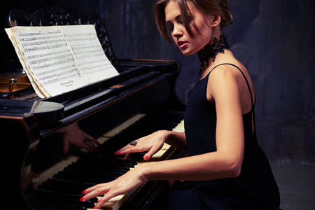 side shot: Mid side shot of well-dressed elegant woman who is using sheet music while sitting tall and proud at the piano with shoulders down