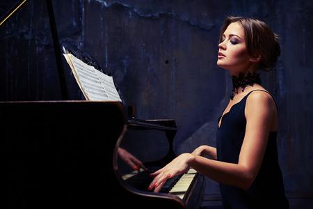 pianista: tiro lateral mediados de mujer sofisticada que domina las llaves. mujer elegante vestido bien que lo está utilizando partituras mientras está sentado alto y orgulloso en el piano con los hombros hacia abajo