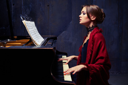 accompaniment: Side mid shot of charming woman in eveningwear with lace black necklace and red scarf playing solo without any accompaniment. Sitting on chair at the piano