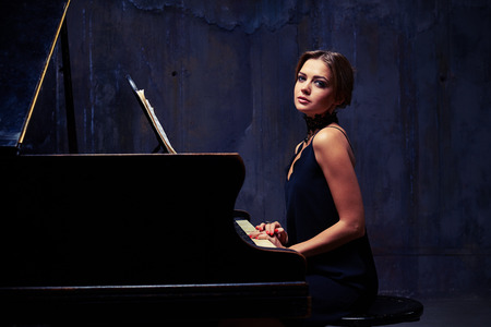 side shot: Mid side shot of inspirited delighted lady is positing while sitting down to the piano. Well-dressed elegant woman who is posing while sitting tall and proud at the piano with shoulders down
