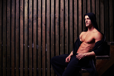 body torso: Side view of young bodybuilder sitting on wooden stairs with bare torso in dim light. His body is firm with strong muscles Stock Photo