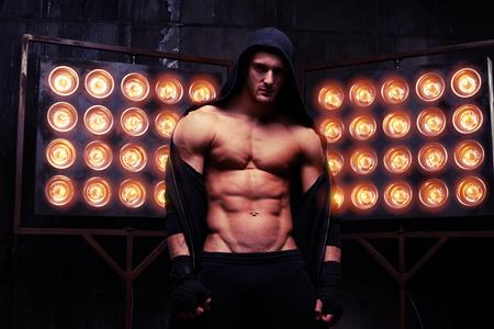 Mid schot van de spier sexy man die poseren tegen de muur met grote roestige versnellingen nadruk op zijn mannelijkheid