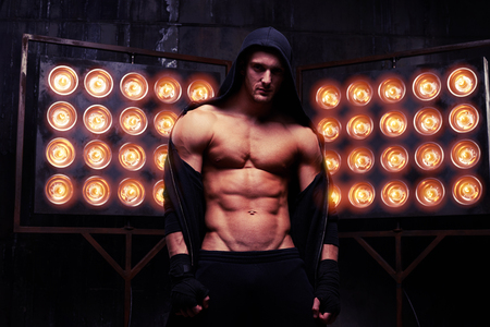 masculinity: Mid shot of muscular sexy male who is posing against the wall with big rusty gears emphasizing his masculinity Stock Photo