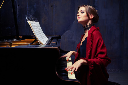 reproducing: Side mid shot of delighted young woman who is making coherent sounds on the piano, enjoying the unity of melody and harmony. Wearing eveningwear with red scarf and lace black necklace Stock Photo