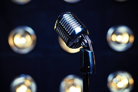 vintage document: Close-up shot of retro silver microphone on spotlights blurred background. Microphone isolated on white background. Classical vintage standing microphone Stock Photo