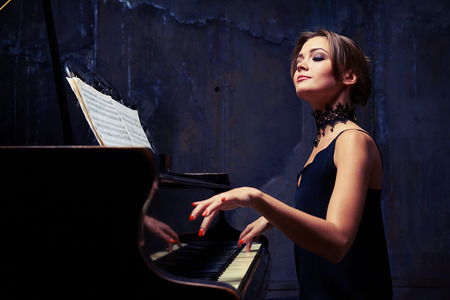 side shot: Mid side shot of elegant woman starts piano performance while sitting isolated in studio. She is using sheet music while sitting tall and proud at the piano with shoulders down