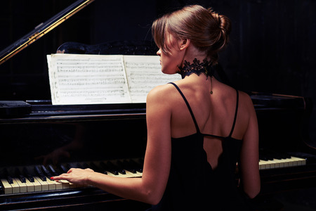 naked woman sitting: Back view of young woman sitting down to the piano in black back naked dress in sombre studio. Glamor beautiful brunette in a black sexy dress with open back Stock Photo