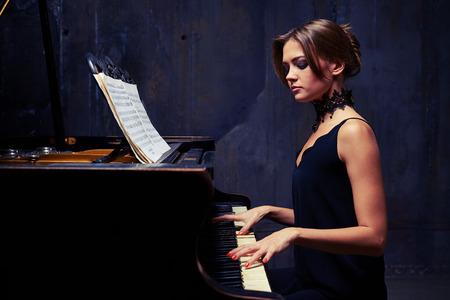 pianista: tiro lateral mediados de modelo de mujer muy joven con labios atractivos pastel de maquillaje, cejas fuertes, la piel brillante limpio y peinado del bollo