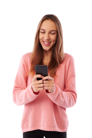Mid shot of delighted youth smiling softy while typing message on smartphone isolated over white background